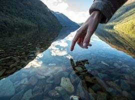 Finger touches surface of mountain lake, the landscape is reflecting on the water.