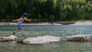 Boy crossing river stepping stones